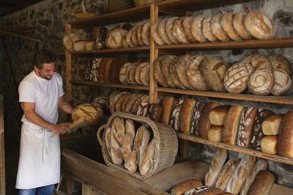 Frank Wolfgang époussetant les pains à la sortie du four.