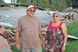 Monique et Serge PIZZOLITO devant leur hangar dévasté... qui a englouti des véhicules anciens.